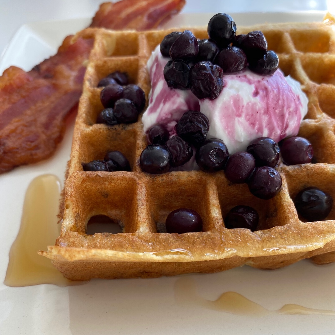 Delicious paleo waffle served with warm blueberries, coconut kefir and a drizzle of maple syrup,